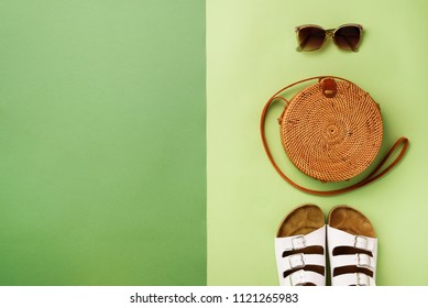 Stylish rattan bag, birkenstocks, sunglasses on green background. Top view with copy space. Trendy bamboo bag and white shoes. Summer fashion flat lay. Creative pop art design.