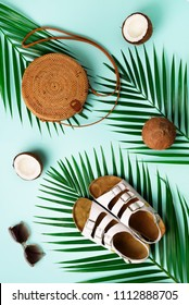Stylish rattan bag, coconut, birkenstocks, palm branches, sunglasses on blue background. Banner. Top view with copy space. Trendy bamboo bag and white shoes. Summer fashion flat lay.
