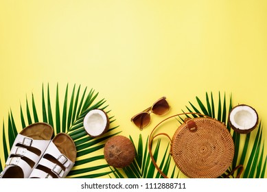 Stylish rattan bag, coconut, birkenstocks, palm branches, sunglasses on yellow background. Banner. Top view with copy space. Trendy bamboo bag and white shoes. Summer fashion flat lay.
