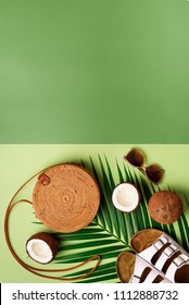 Stylish rattan bag, coconut, birkenstocks, palm branches, sunglasses on olive green background. Banner. Top view with copy space. Trendy bamboo bag and white shoes. Summer fashion flat lay.