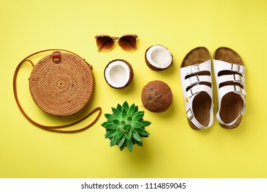 Stylish rattan bag, coconut, birkenstocks, palm branches, succulent, sunglasses on yellow background. Banner. Top view with copy space. Trendy bamboo bag and white shoes. Summer fashion flat lay.