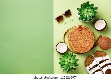 Stylish rattan bag, coconut, birkenstocks, succulent, sunglasses on yellow background. Banner. Top view with copy space. Trendy bamboo bag and white shoes. Summer fashion flat lay.