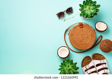 Stylish rattan bag, coconut, birkenstocks, succulent, sunglasses on blue background. Banner. Top view with copy space. Trendy bamboo bag and white shoes. Summer fashion flat lay.