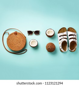 Stylish rattan bag, coconut, birkenstocks, palm branches, sunglasses on blue background. Square crop. Top view with copy space. Trendy bamboo bag and white shoes. Summer fashion flat lay.