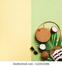 Stylish rattan bag, coconut, birkenstocks, palm branches, sunglasses on olive green background. Square crop. Top view, copy space. Trendy bamboo bag and white shoes. Summer fashion flat lay.