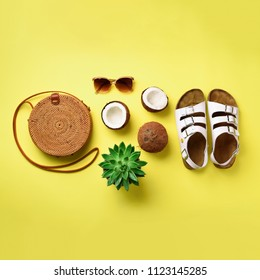 Stylish rattan bag, coconut, birkenstocks, palm branches, sunglasses on yellow background. Square crop. Top view with copy space. Trendy bamboo bag and white shoes. Summer fashion flat lay.