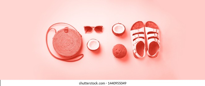 Stylish rattan bag, coconut, birkenstocks, palm branches, sunglasses on coral color background. Top view with copy space. Trendy bamboo bag and white shoes. Summer fashion flat lay.
