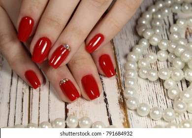 stylish red manicure on a background of beautiful texture