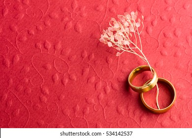 Stylish Red Wedding Background - Two wedding rings on embossed texture, copy space for text