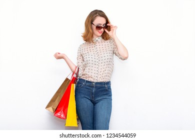 Stylish red-haired woman standing on a light background with glasses and casual clothes, holding bags after shopping. The modern concept of shoping, selling, discounts, fashion.