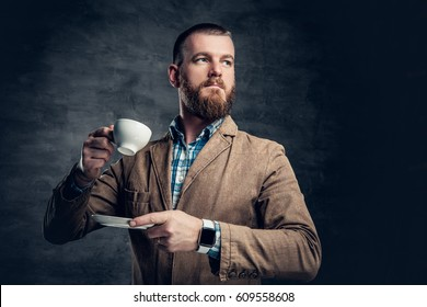 Stylish redhead bearded hipster male drinks coffee.
