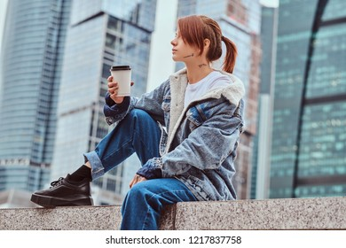 Stylish redhead hipster girl with tattoo on her face wearing denim coat holding takeaway coffee sitting in front of skyscrapers in Moskow city at cloudy morning.