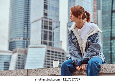 Stylish redhead hipster girl with tattoo on her face wearing denim jacket sitting in front of skyscrapers in Moskow city at cloudy morning.