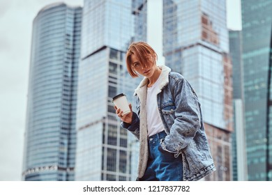 Stylish redhead hipster girl with tattoo on her face wearing denim jacket holding takeaway coffee in front of skyscrapers in Moskow city.