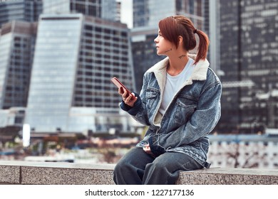 Stylish redhead hipster girl with tattoo on her face wearing denim jacket using a smartphone sitting in front of skyscrapers in Moskow city at cloudy morning.