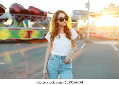 Stylish redhead young hipster woman in stylish sunglasses in a trendy white t-shirt in blue trendy jeans posing outdoors on the background of carousels. American girl enjoys a bright summer sunset.