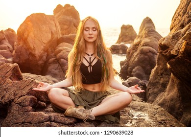 stylish redheaded chestnut blonde young girl in indie bohemian bo-ho style clothes black stylish top.boho woman long hair,makeup and green feathers in head practicing yoga asanas on the rocks by sea