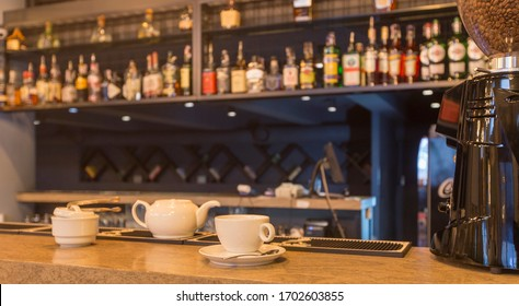 Stylish restaurant in a loft style, bar with tea set, shelves with bottles and glasses, bar equipment, copy space, panorama