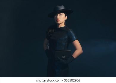 Stylish retro 1940 asian fashion woman. Holding handbag. Wearing hat.