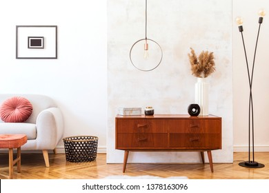 Stylish and retro interior of living room with design commode, gray sofa, round pendant lamp, vintage footrest, elegant accessories and mock up photo frames. Minimalistic home decor of sitting room.