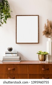 Stylish and retro space of home interior with mock up poster frame, vintage cupboard with elegant gold accessories, flowers in vase, plants and books. Nice home decor. Minimalistic concept. Template.