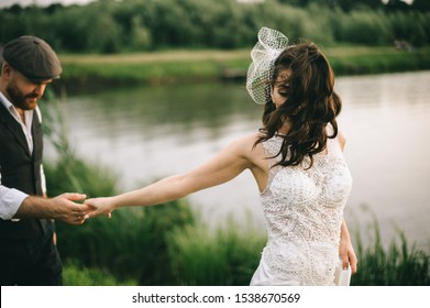 Stylish retro wedding couple, bride, groom walking in a field near the lake