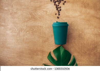 Stylish reusable eco coffee cup  on wooden background with coffee beans and green monstera leaf. Flat lay with copy space. Zero waste concept. Ban single use plastic. Sustainable lifestyle
