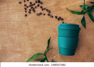 Stylish reusable eco coffee cup  on wooden background with coffee beans and green bamboo leaves. Ban single use plastic. Zero waste concept, flat lay. Sustainable lifestyle. Natural bamboo cup