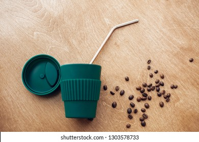 Stylish reusable eco coffee cup and metallic steel straws on wooden background with coffee beans. Ban single use plastic, zero waste concept, flat lay. Sustainable lifestyle. Natural bamboo cup