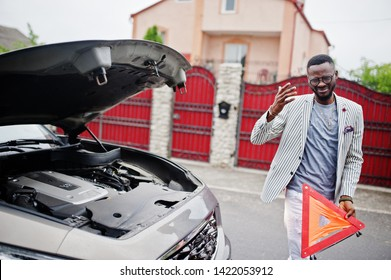 Stylish and rich african american man stand in front of a broken suv car needs assistance looking under opened hood and hold e,ergency triangle.