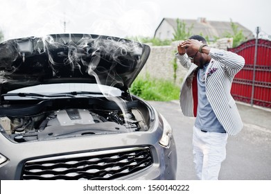 Stylish and rich african american man stand in front of a broken suv car needs assistance looking under opened hood with smoke.