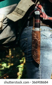 stylish rich knife on traveler backpack in sunny forest in the mountains