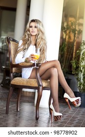 Stylish rich slim girl resting sitting holding orange drink in sexy dress with healthy glossy hair in luxurious interior at hotel villa apartment. Fashion glamorous shot vacation resort spring-summer