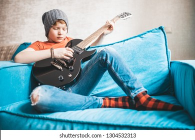 Stylish rock and roll kid with a black electric guitar sits in a chair and plays music