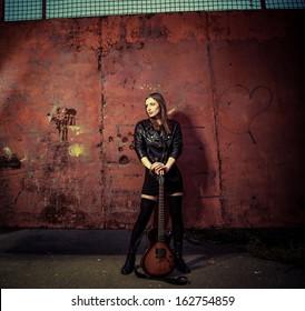 stylish rock woman in black at rusty gate