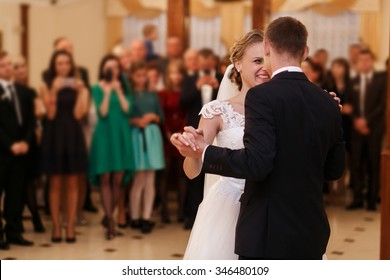 Stylish romantic young couple dancing waltz on their wedding day in luxury restaurant hall against the backdrop of crowds. Beautiful blonde bride in white dress.
