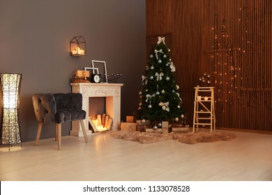 Stylish room interior with Christmas tree and decorative fireplace