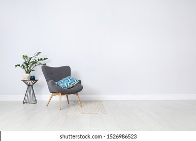 Stylish room interior with comfortable armchair and plant near white wall. Space for text
