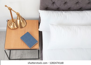 Stylish room interior with comfortable bed and nightstand, above view