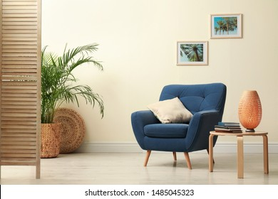 Stylish room interior with comfortable furniture and plant near beige wall