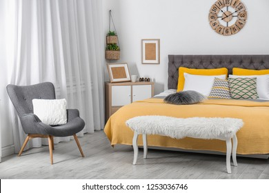 Stylish room interior with large comfortable bed