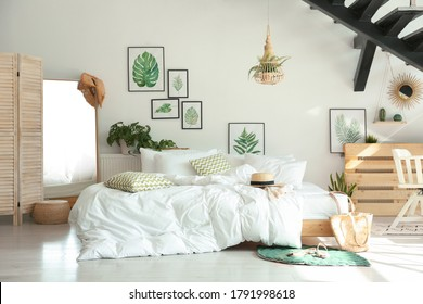 Stylish room interior with large comfortable bed under stairs