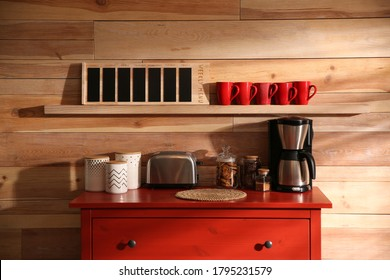 Stylish room interior with modern coffeemaker and toaster on red chest of drawers