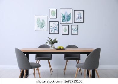 Stylish room interior with modern table, chairs and paintings of tropical leaves. Idea for design - Shutterstock ID 1692913105