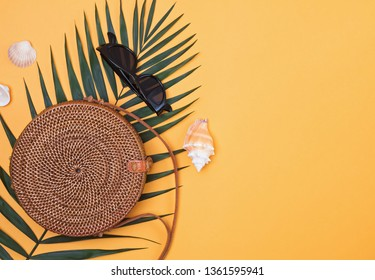 Stylish round straw handbag with palm leaf, sunglasses and seahells on the bright yellow background, top view.