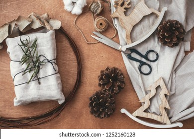 Stylish rustic gift wrapped in linen fabric with green branch on wooden table with pine cones, reindeer, scissors, twine, cotton. Flat lay. Simple eco presents plastic free. Zero waste christmas