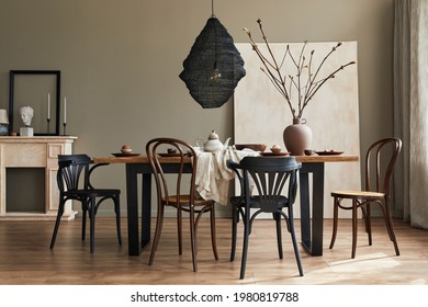 Stylish rustic interior of dining room with walnut wooden table, retro chairs, decoration, fireplace, dried flower, candlestick mock up picture frame and carpet in minimalist home decor. Template. - Shutterstock ID 1980819788