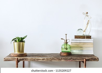 Stylish scandinavian composition of wooden console with books, plants and accessories. Modern composition of home interior with copy space.