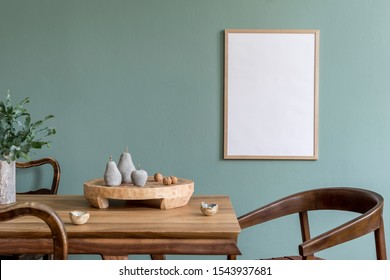 Stylish scandinavian dining room interior with mock up poster frame, wooden table, furniture, cup of coffee, plant , cement fruits, nuts and elegant accessories.  Template. Modern home decor.