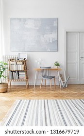 Stylish scandinavian home decor of interior with creative wooden desk, bamboo bookstand with accessories, books and plants  Open space and living room. Brown wooden parquet and stylish carpet.